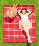 女孩在夏天给放置在野餐毯子穿衣 免版税库存图片