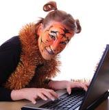 女孩在外观上与笔记本的一只老虎。 库存照片