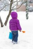 女孩在多雪的前院 免版税库存照片