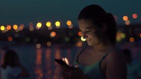 女孩在夜城市时使用一个智能手机,当走 股票录像