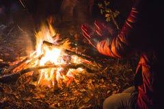 女孩在夜森林里温暖她的从火的手 免版税库存照片