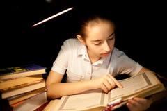 女孩在夜黑暗的阅读书在图书馆 免版税库存照片
