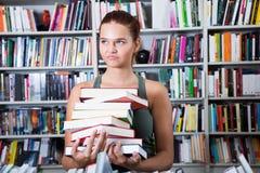 女孩在大学图书馆里选择一本书 免版税图库摄影