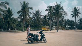 女孩在大正方形站立在印象深刻的黑摩托车旁边 影视素材