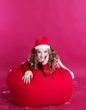 女孩在大红色圣诞节袋子说谎 免版税库存照片