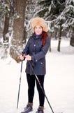 女孩在天空的冬天森林里 免版税库存图片