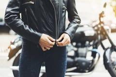 女孩在太阳火光大气城市,行家骑自行车的人女性手特写镜头解开在背景摩托车的黑皮夹克 免版税库存图片