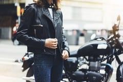 女孩在太阳火光大气城市,行家骑自行车的人女性手特写镜头解开在背景摩托车的黑皮夹克 图库摄影