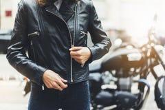 女孩在太阳火光大气城市,行家骑自行车的人女性手特写镜头解开在背景摩托车的黑皮夹克 库存照片