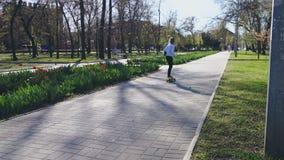 女孩在太阳的光芒的一个公园中间乘坐一个黄色滑板 影视素材