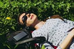 女孩在太阳镜的绿草说谎 免版税库存图片