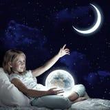女孩在她的床和发光的地球上 库存图片