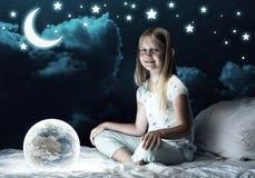 女孩在她的床和发光的地球上 免版税库存图片