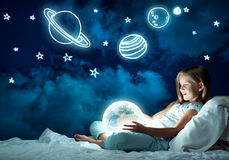 女孩在她的床和发光的地球上 库存照片