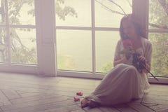 女孩在她的手上坐与她回到窗口并且拿着一朵玫瑰花 白色礼服的少妇坐  库存图片