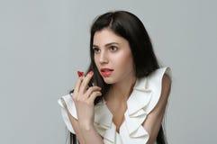 女孩在她的手上拿着唇膏象雪茄 免版税图库摄影