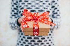 女孩在她的手上拿着圣诞节礼物 免版税库存照片