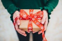 女孩在她的手上拿着圣诞节礼物 免版税图库摄影