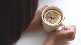 女孩在她的手上拿着杯子与切片的金黄茶芬芳柠檬 股票视频