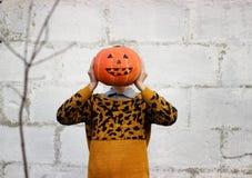 女孩在她的手上拿着而不是她的头的滑稽的橙色南瓜头特写镜头 免版税库存照片