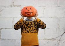 女孩在她的手上拿着而不是她的头的滑稽的橙色南瓜头特写镜头 免版税库存图片