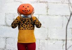 女孩在她的手上拿着而不是她的头的滑稽的橙色南瓜头特写镜头 免版税图库摄影