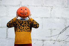 女孩在她的手上拿着而不是她的头的滑稽的橙色南瓜头特写镜头 库存图片
