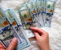 女孩在她的手上拿着金钱 一百美元现金 库存图片