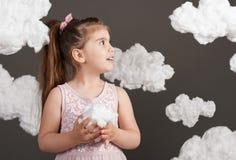 女孩在她的手上的拿着一朵云彩,射击在灰色背景的演播室 库存照片