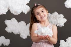 女孩在她的手上的拿着一朵云彩,射击在灰色背景的演播室 免版税库存照片