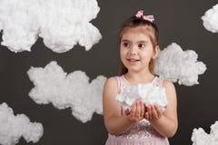 女孩在她的手上的拿着一朵云彩,射击在灰色背景的演播室 免版税图库摄影