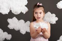 女孩在她的手上的拿着一朵云彩,射击在灰色背景的演播室 免版税库存图片