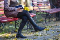 女孩在她的手上读一本书并且拿着纸杯子, autu 免版税库存照片
