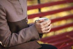 女孩在她的手上读一本书并且拿着纸杯子, autu 图库摄影