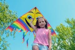 女孩在她的手和微笑上拿着一只明亮的风筝反对天空蔚蓝 夏天、自由和愉快的童年的概念 免版税库存图片