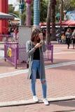 女孩在她的手机站立并且看 库存图片
