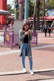 女孩在她的手机站立并且看 免版税库存图片