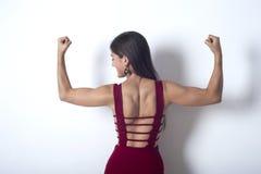 女孩在她的胳膊显示肌肉 免版税图库摄影