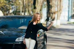 女孩在她的brocked汽车附近的中止汽车 库存图片