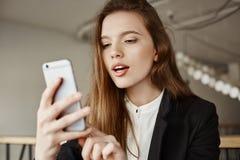 女孩在她的selfie上把过滤器放 坐在咖啡馆的时髦的现代欧洲学生室内射击,更新她的外形 免版税图库摄影