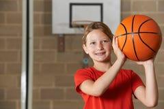 女孩在学校健身房的射击篮球 免版税库存图片