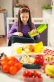 女孩在学校的一个袋子投入快餐 免版税库存照片