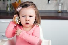 女孩在家使用与梳子-刻画的2岁在电话的一次情感交谈 免版税图库摄影