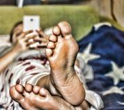 女孩在家使用在长沙发的一个白色智能手机美国国旗的颜色 免版税图库摄影
