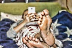 女孩在家使用在长沙发的一个白色智能手机美国国旗的颜色 图库摄影