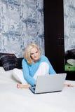 女孩在家坐与膝上型计算机的床 库存图片