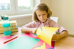 女孩在家坐在桌上靠近窗口,剪色纸,做创造性 学校,教育,知识和 免版税库存图片