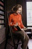 女孩在家庭书库里 免版税库存图片