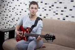 女孩在家弹电吉他 红色吉他在美丽的妇女的手上公寓的 免版税库存图片