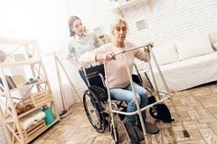 女孩在家护理年长妇女 妇女设法从轮椅站起来 免版税库存图片